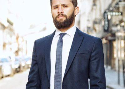 William portant un costume cravate bleu marine, pose dans les rues du 1er arrondissement de Paris.